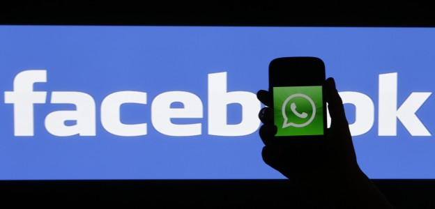 Woman holds a smartphone displaying WhatsApp's logo in front of the screen with the Facebook logo in this photo illustration taken in Prague